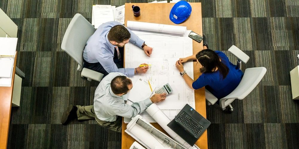 Three people talk about building plans in an office